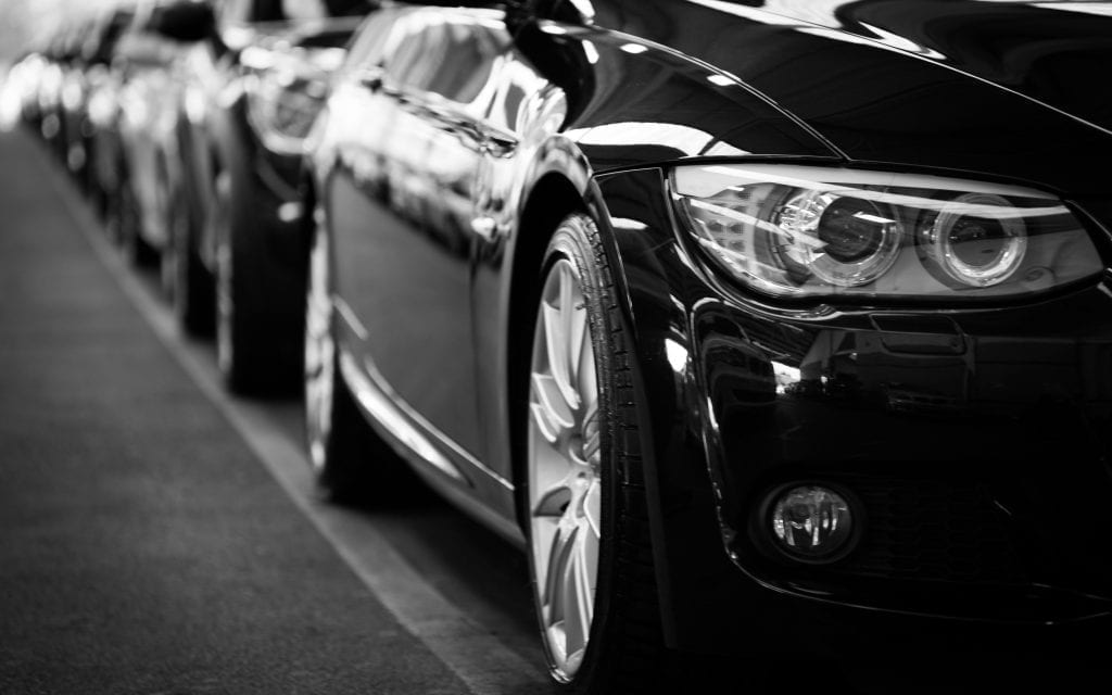 a lineup of cars in black and white