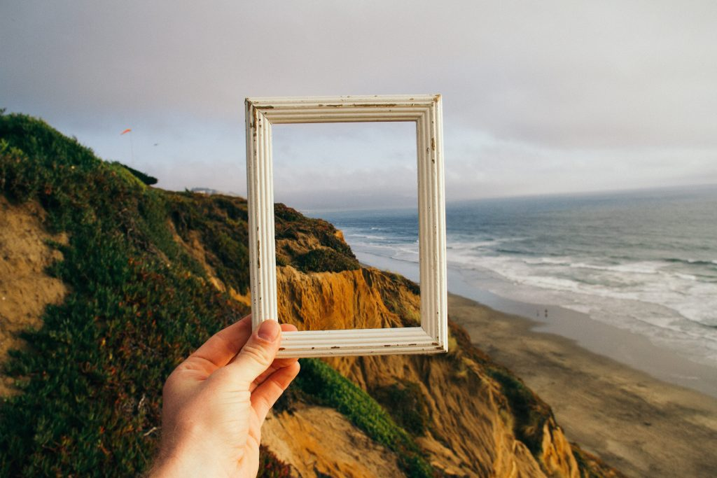 the bigger picture, a picture showing a human hand holding a frame through and outside which a beach can be seen